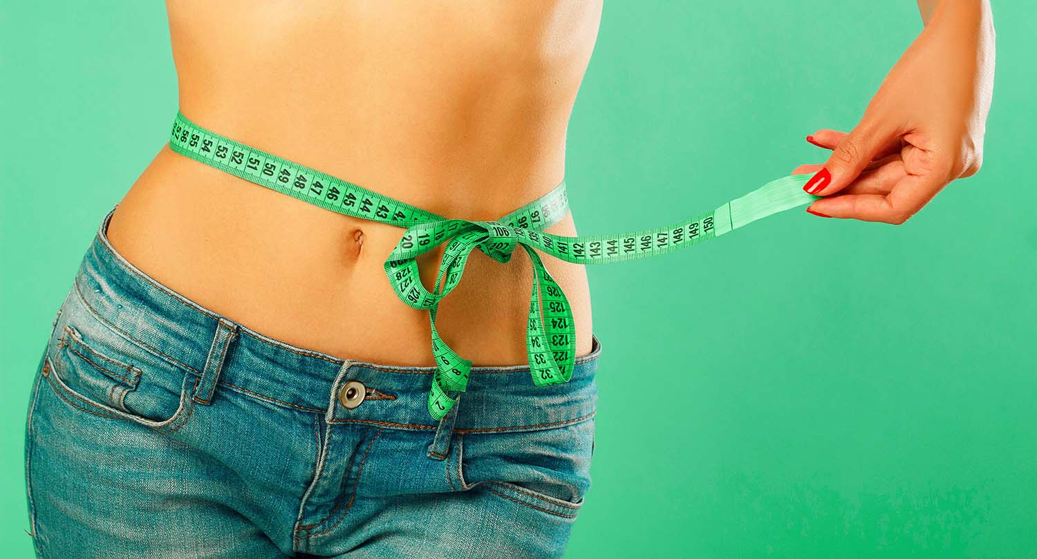 Woman measuring fat loss around waist